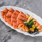 Seafood platter with salmon slice, shrimp, slices fish fillet, decorated with olives and lemon in plate over rustic background. Mediterranean appetizers. Top stock photos