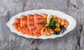 Seafood platter with salmon slice, shrimp, slices fish fillet, decorated with olives and lemon in plate over rustic background. Mediterranean appetizers. Top royalty free stock images