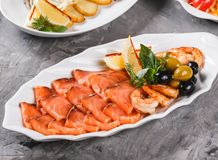Seafood platter with salmon slice, shrimp, slices fish fillet, decorated with olives and lemon in plate over rustic background. Mediterranean appetizers stock photography