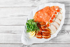 Seafood platter with salmon slice, smoke sturgeon, quail eggs with red caviar, slices fish fillet with arugula on wood background Stock Images