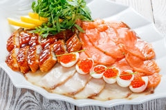 Seafood platter with salmon slice, smoke sturgeon, quail eggs with red caviar, slices fish fillet with arugula on wood background Royalty Free Stock Photography