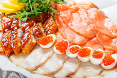 Seafood platter with salmon slice, smoke sturgeon, quail eggs with red caviar, slices fish fillet on wooden background Stock Images