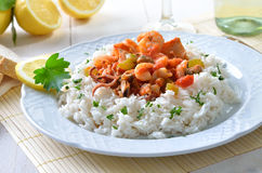 Seafood ragout. With basmati rice, white wine and lemons in the background Royalty Free Stock Photo