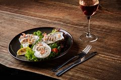 Seafood. Restaurant cuisine, healthy delicatessen food. Oysters, shrimps, octopus in white cream sauce in the shell of Royalty Free Stock Photography