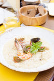 Seafood risotto with shrimp, tomatoes and basil. In the restaurant Royalty Free Stock Image
