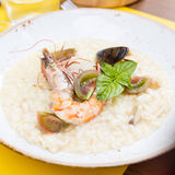 Seafood risotto with shrimp, tomatoes and basil. In the restaurant Royalty Free Stock Photography