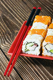 Seafood rolls and chopsticks on a red plate Royalty Free Stock Photos