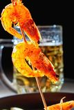 Seafood. Grilled fried shrimps on wooden skewers with spices and oil. On background of mug with beer, cast-iron frying pan. Stock Photography
