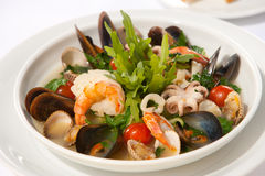 Seafood salad. With arugula and cherry tomatoes in a deep white plate Stock Photography