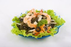 Seafood salad. On a white background. Contains shrimps, sea algae's, anchous, black olives and carrot Stock Photo