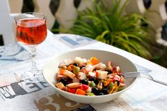 Seafood salad and glass of rose wine in outdoor cafe in Spain.  Stock Image