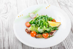 Seafood salad with mussels, squids, octopus, arugula, lettuce and cherry tomatoes on wooden background close up Stock Images