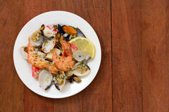 Seafood salad on plate on brown background Royalty Free Stock Images