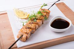 Seafood salmon grilled on a skewer. Served on wooden board royalty free stock images