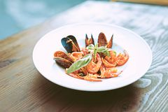 Italian meal with tomato sauce and seafood placed on deep plate. Seafood with sauce. Italian meal with tomato sauce and seafood placed on deep plate and royalty free stock image
