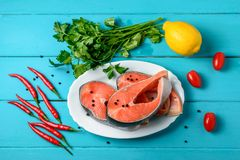 Salmon with chili pepper, tomatoes and lemon Royalty Free Stock Image
