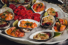 Seafood. Shellfish. Raw scallops with lemon, cilantro. And white wine on black stone slate plate Stock Image