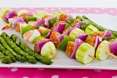Seafood Skewers are Ready to go on the barbecue. Salmon cubes and Shrimp complimented with vegetables on skewers. Ready to cook. Red onions, zucchini, green Royalty Free Stock Photo