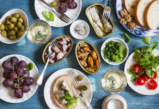 Seafood snacks table - canned sardines, mussels, octopus, grape, olives, tomato and two glasses white wine on wooden table, top vi. Ew. Flat lay Royalty Free Stock Photography