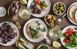 Seafood snacks table - canned sardines, mussels, octopus, grape, olives, tomato and two glasses white wine on wooden table, top vi Royalty Free Stock Photos