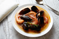 Seafood soup Bouillabaisse with fish, prawns, mussels tomato, lobster. Traditional France dish. White wooden background Royalty Free Stock Image