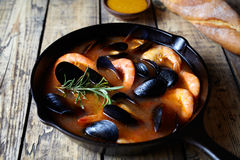 Seafood soup bouillabaisse. Mussels and shrimp in tomato sauce. The traditional dish of Marseilles. Rustic style. Stock Photos