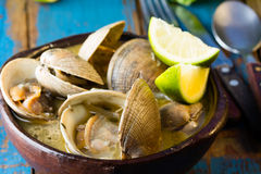 Seafood soup of clams Paila marina in clay bowl. Seafood soup of clams in clay bowl on wooden blue background.  Mariscal or paila marina Royalty Free Stock Photography