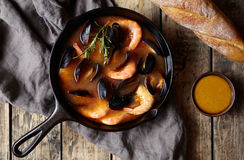 Seafood soup with fish, prawns, mussels tomato, lobster. Bouillabaisse. Rustic style background. Flat lay. Stock Image