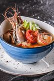 Seafood soup with langoustine, mussels, squid, fillet salmon, shrimp and celery in bowl over dark background. Healthy food, diet. Food, mediterranean food stock photos