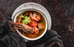 Seafood soup with langoustine, mussels, squid, fillet salmon, shrimp and celery in bowl over dark background. Healthy food, diet. Food, mediterranean food. Top royalty free stock photos