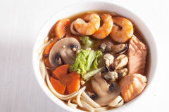 Seafood soup with noodles and mushrooms shrimp, salmon, mussels, carrots, lettuce Royalty Free Stock Photography
