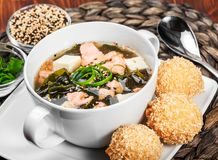 Seafood Soup with salmon, cheese, seaweed, sesame and bread on plate on wooden background. Mediterranean food. Ingredients on table stock image