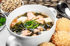 Seafood Soup with salmon, cheese, seaweed, sesame and bread on plate on wooden background. Mediterranean food. Ingredients on table stock photography