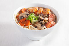 Seafood soup shrimp mussels pasta fish mushrooms in a bowl isolated on white background Stock Photo