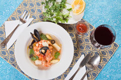 Seafood soup with shrimps and mussels. On blue ornate table-cloth Stock Image