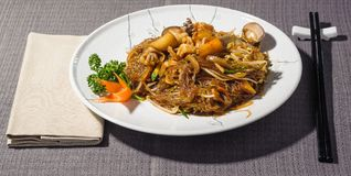 Seafood soya spaghetti, modern and fusion japanese cousine. Seafood soya spaghetti with clams, shrimps, squid, crab pulp, carrots and courgettes, seasoned with Stock Image