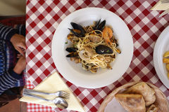 Seafood spaghetti on red checker board table. Top view stock photos