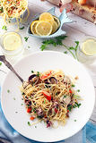 Seafood Spaghetti on a White Table with Glasses of Lemon Water Royalty Free Stock Image