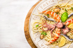 Seafood spaghetti with  whole baby octopus and big Shrimp in plate , close up Royalty Free Stock Photo