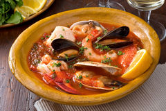 Seafood Stew. A hearty bowl of rustic mediterranean seafood stew with lobster, shrimp, mussels, clams, scallops, and white fish Stock Images