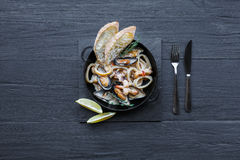 Seafood Stew on dark wood background, top view, copy space Royalty Free Stock Photography