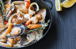 Seafood Stew in Saucepan closeup on dark wood background Stock Photos