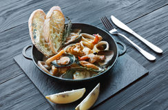 Seafood Stew in Saucepan on dark wood background Stock Images
