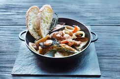 Seafood Stew in Saucepan on dark wood background Royalty Free Stock Images