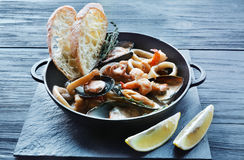 Seafood Stew in Saucepan on dark wood background Royalty Free Stock Photos