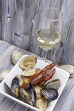 Seafood Stew with Wine. Dish of seafood stew with a glass of white wine Stock Photos
