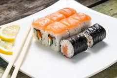 Seafood sushi rolls in white plate with chopsticks Royalty Free Stock Image