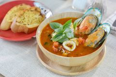 Seafood tomato soup served with garlic bread on cutting board an. D wood table. White, meal, tasty, dinner, plate, cooking, lunch, restaurant, cuisine, dish royalty free stock image