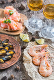 Seafood with two glasses of white wine on the wooden table Stock Photos