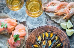 Seafood with two glasses of white wine on the wooden table Stock Image